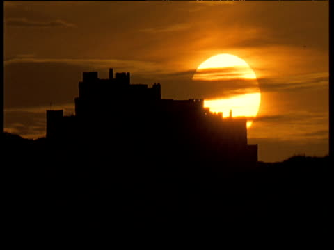 Sun surrounded by wisps of clouds sets behind silhouette of Bamburgh castle in amber sky, Northumberland