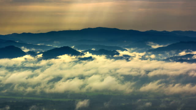 Sunbeams and Fog rolls across flowing over mountains