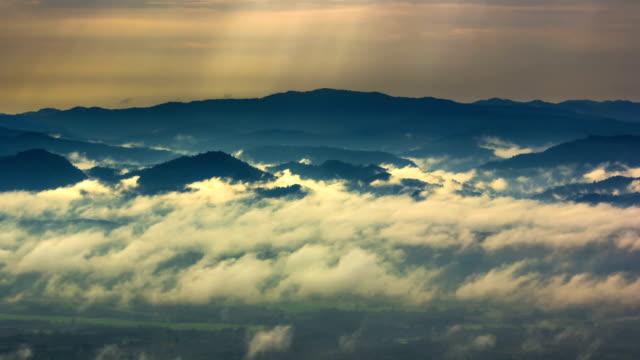 Sonnenstrahlen und Nebel breitmacht über fließende auf die Berge