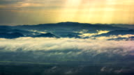Sunbeams and Fog rolls across flowing over mountains,Time lapse