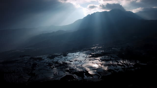Sunbeams drift over rice paddy terraces, Yuanyang, Yunnan, China