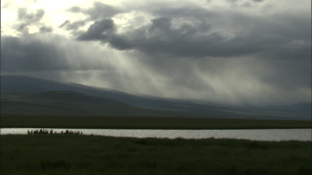 Sunbeams shine through black clouds over hills and lake, Bayanbulak grasslands.