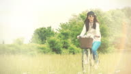 Sunlight and cycling. Young woman riding a retro bike though a meadow. Slow motion.