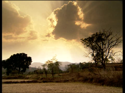 Sunlight bursting behind gathering monsoon clouds pan right to village landscape India
