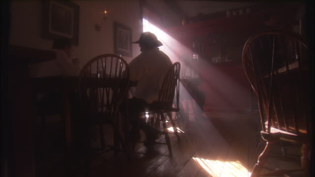 Sunlight filters into a 19th century tavern where a waiter serves two men at a table.