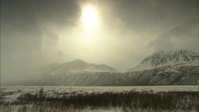 Sunlight filters through dense clouds above snowy mountains in Alaska.