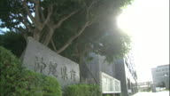 Sunlight illuminates a stone sign near the Okinawa Prefectural Government office in Japan.