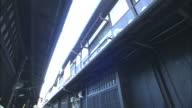 Sunlight penetrates into an alleyway between townhouses.