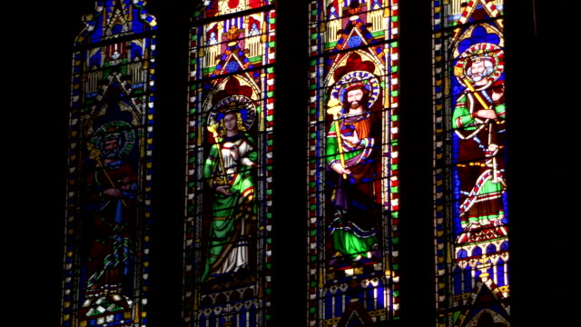 Sunlight slants through stained glass windows in Ely Cathedral. Available in HD.