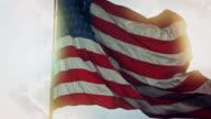 Solbelysta amerikanska flaggan blåser i vinden