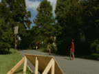 Sunny suburban street. A boy wearing a crash helmet approaches a wooden ramp on a skateboard. He hits the ramp but loses his skateboard and flies through the air, landing in a heap on the grass. Long Island, New York, USA