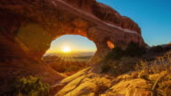 T/L 8K Sunrise over a sandstone arch formations