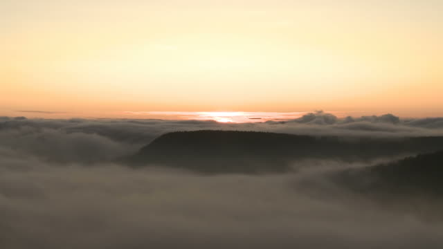 sunrise over landscape covered in fog