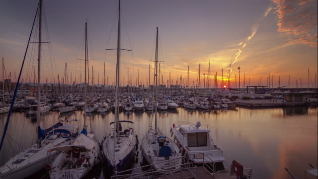 Sunrise timelapse view of sea bay with yachts in Barcelona, Spain