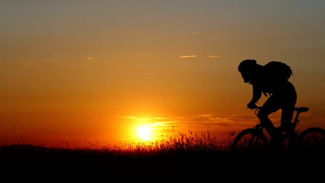 Sunset and rear view of mountain cyclist riding-slow motion