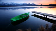sunset and tranquil scene with row boat at lake hopfensee