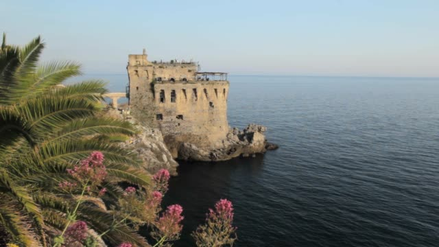 Sunset at ancient Norman Tower of Maiori with quite sea, palm leaves and flowers