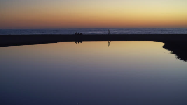Sunset at the Venice Beach, Santa Monica, California, USA. Some people make exercise and jogging in the background.