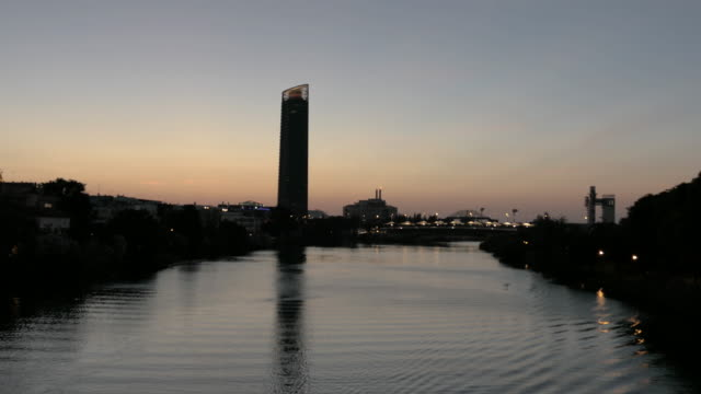 sunset from isabel II bridge triana watching pelli tower and expo building in seville spain
