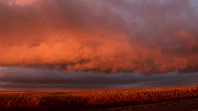 Sunset gives looming clouds and wheat fields orange hue Scott City Kansas 8 May 2008
