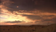 A sunset illuminates clouds above the Kalahari Desert.