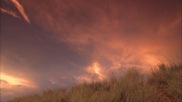 A sunset illuminates clouds above the Kalahari Desert.