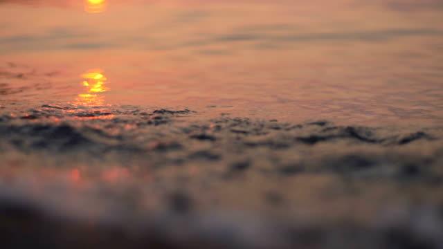 Sunset on the beach. Sun reflecting on waves