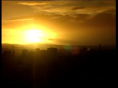 Sunset over Edinburgh pan right to silhouette of Edinburgh Castle
