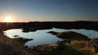 WS PAN Sunset over reflective lake surrounded by volcanic rock / Reykjavik, Borgarfjaroarsysla, Iceland