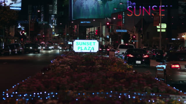 HA Sunset Plaza illuminated after dark and busy with flowing street traffic / West Hollywood, California, United States