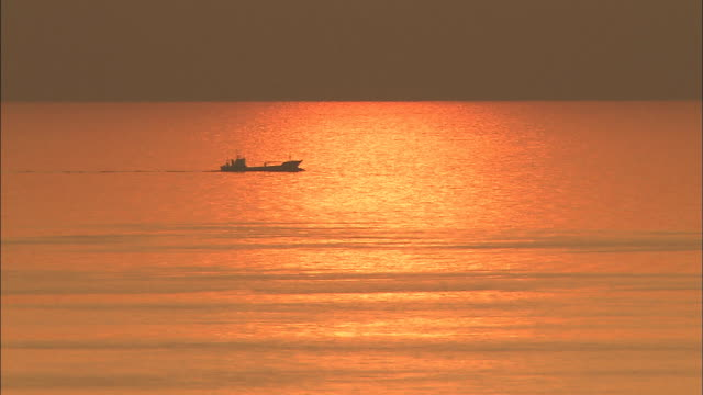 Sunset reflected in sea as boat passes by, Nagasaki