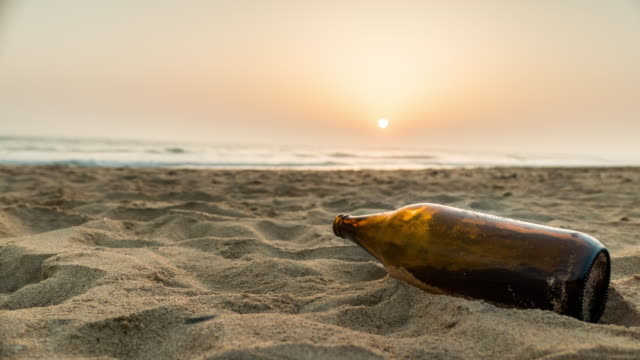 sunset timelapse with beer bottle in the sand in the beach of cadiz españa