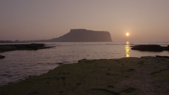 Sunset view of Seongsanilchulbong Tuff Cone (Korea Natural Monument 420) and surrounding seascape