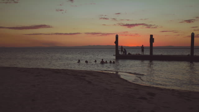 Sunset with a pier and a calm sea, in Bribie Island, Australia
