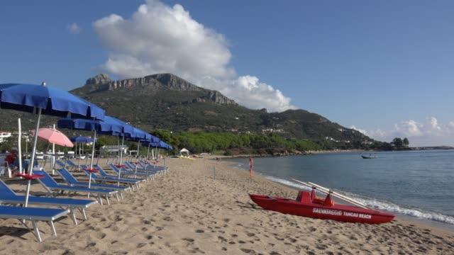 Sunshades and lifeboat at sandy beach