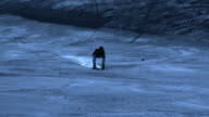 Super slow motion of skier skiing downhill by night.