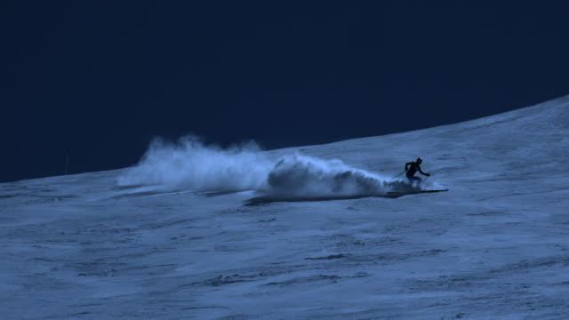 Super slow motion of skier spreading powder snow by night.