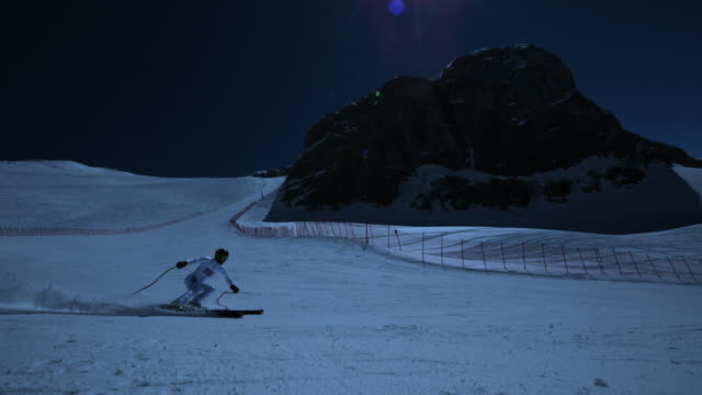 Super slow motion of skier spreading snow into the camera.