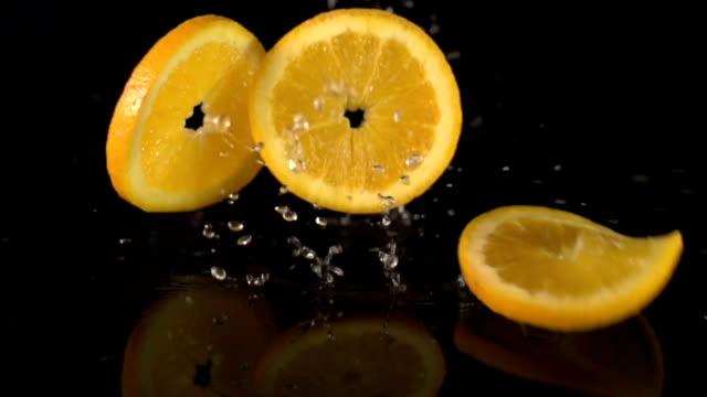 Super Slow Motion: Orange Slices falling splashing Water