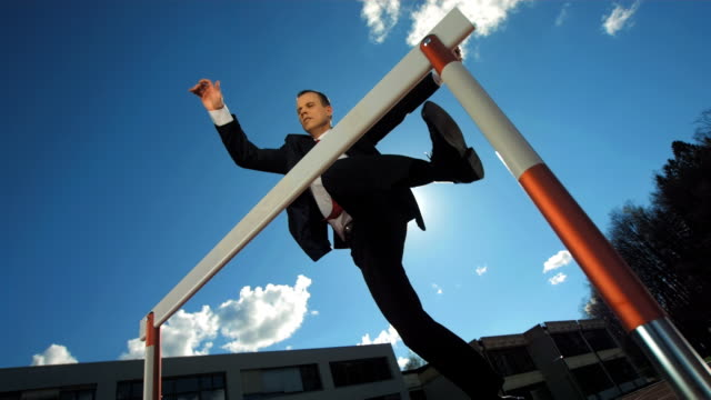 HD Super Slow-Mo: Businessman Jumping Over A Hurdle