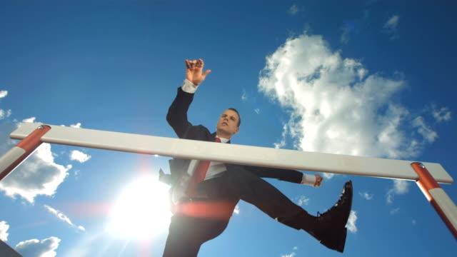 HD Super Slow-Mo: Executive Jumping Over A Hurdle