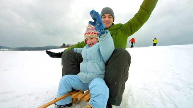 HD Super Slow-Mo: Father And Daughter Sledging Down The Hill