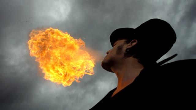 HD Super Slow-Mo: Fire Breather Against Cloudy Sky