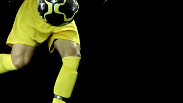 HD Super Slow-Mo: Kicking A Ball On Black Background