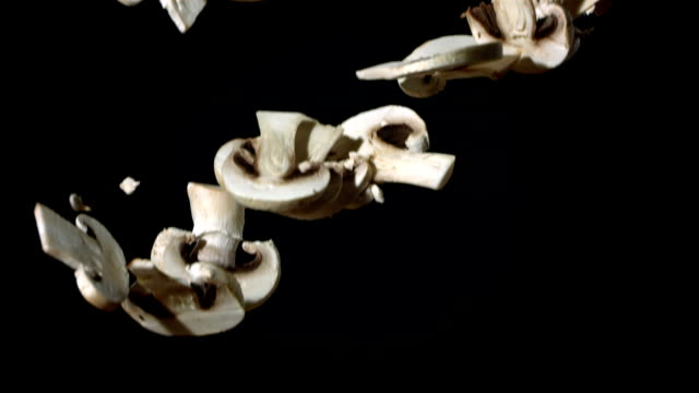 HD Super Slow-Mo: Mushrooms Falling Over Black Background