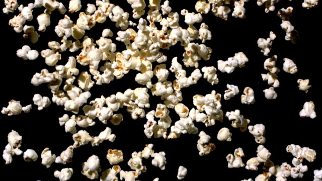 HD Super Slow-Mo: Popcorn Falling Over Black Background