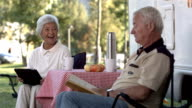 HD Super Slow-Mo: Seniors Having Fun Reading At Campsite