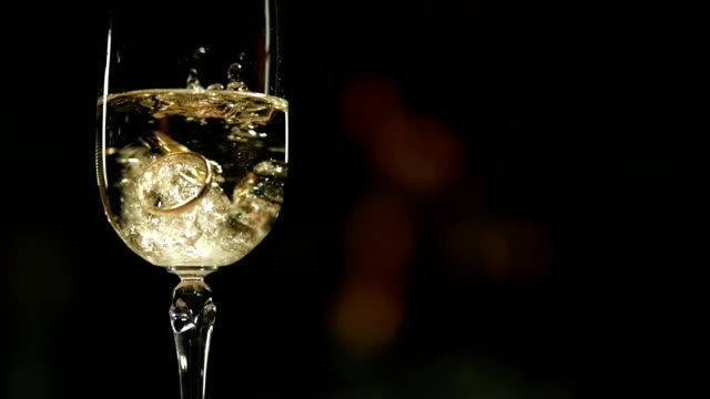 HD Super Slow-motion: Fedi nuziali In un bicchiere di Champagne