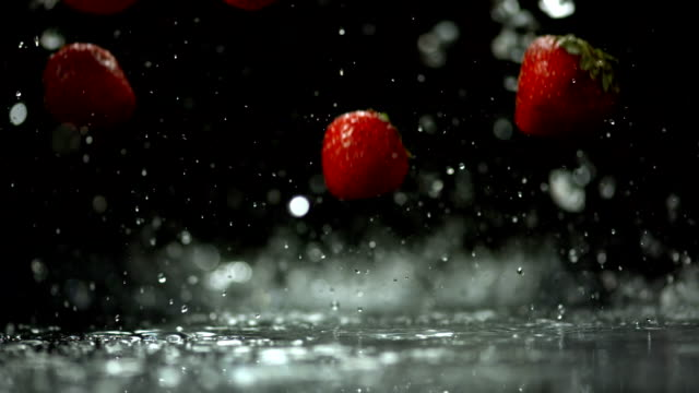 HD Super Slow-Mo: Wet Strawberries Falling On Surface