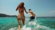 HD Super Slow-Mo: Young Couple Splashing Into The Sea